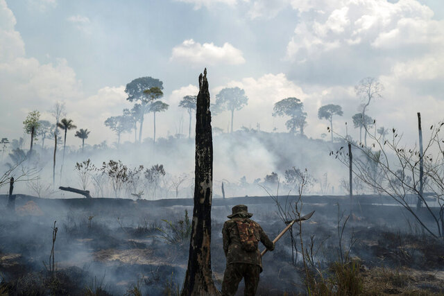 FILE - In this Sept. 3, 2019, file photo, Brazilian soldier puts out fires at the Nova Fronteira region in Novo Progresso, Brazil. In 2019, the forest around the town of Novo Progresso erupted into flames — the first major blazes in the Brazilian Amazon's dry season and spurred global outrage against the government's inability or unwillingness to protect the rainforest. President Jair Bolsonaro pledged to control burning in the forest in 2020, but smoke is again thick in the area. (AP Photo/Leo Correa, File)