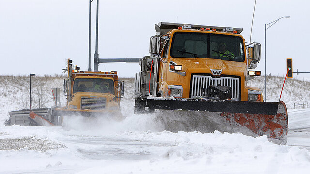 Plows from the City of Rapid City Streets Department work their way along Fifth Street in Rapid City, S.D., Thursday ,April 2, 2020, to clear snow and ice after a winter storm moved into the Black Hills region on Wednesday. (Jeff Easton/Rapid City Journal via AP)
