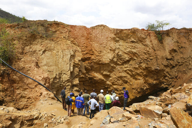 Government officials are seen at the sight of an abandoned mine where artisanal miners are trapped underground in Bindura about 70 kilometres northeast of the capital Harare, Tuesday, Dec, 1, 2020.  Artisanal miners illegally digging for gold in a disused shaft blasted a support pillar resulting in them being trapped. A government rescue agency says 10 miners are still trapped under the rabble with hopes of finding survivors diminishing after rescuers retrieved one body on Monday according to a government spokesman.(AP Photo/Tsvangirayi Mukwazhi)