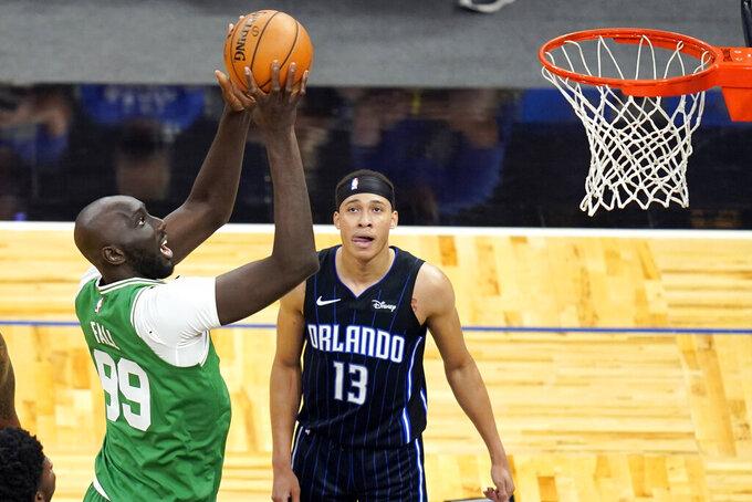 Boston Celtics center Tacko Fall (99) makes a shot in front of Orlando Magic guard R.J. Hampton (13) during the second half of an NBA basketball game, Wednesday, May 5, 2021, in Orlando, Fla. (AP Photo/John Raoux)
