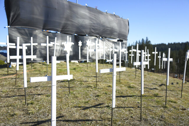 The 73 crosses signifying COVID-19 deaths in Nevada County, sit on the hill next to Old Barn Storage Tuesday, Jan. 19, 2021 in Grass Valley, Calif. (Elias Funez/The Union via AP)