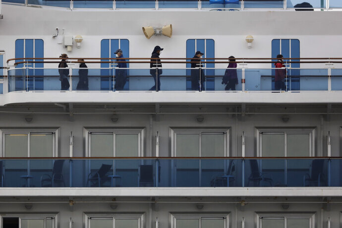 A group of quarantined passengers exercise on the Diamond Princess cruise ship Saturday, Feb. 15, 2020, in Yokohama, near Tokyo. A viral outbreak that began in China has infected more than 67,000 people globally. The World Health Organization has named the illness COVID-19, referring to its origin late last year and the coronavirus that causes it. (AP Photo/Jae C. Hong)