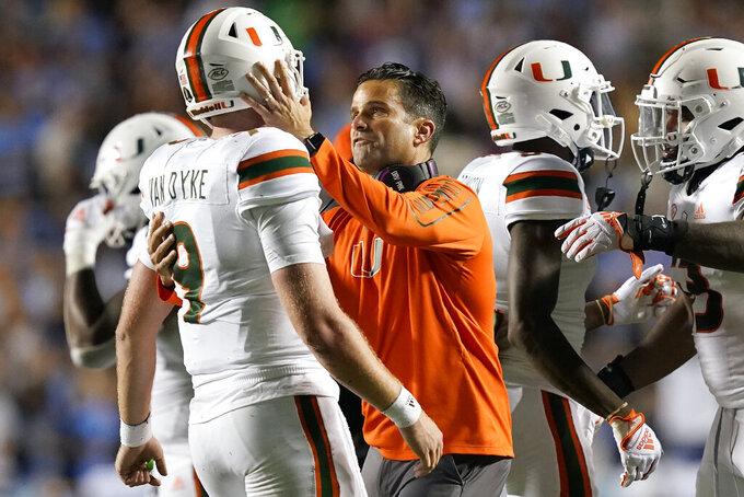 Miami head coach Manny Diaz, center, consoles quarterback Tyler Van Dyke (9) following an NCAA college football game against North Carolina in Chapel Hill, N.C., Saturday, Oct. 16, 2021. (AP Photo/Gerry Broome)