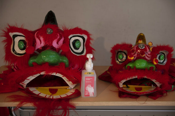 In this Feb. 13, 2020, photo, a bottle of hand sanitizer is placed next to lion masks at an information center in Yokohama's Chinatown, near Tokyo. A top Olympic official made clear Friday the 2020 Games in Tokyo will not be cancelled despite the virus that has spread from China. (AP Photo/Jae C. Hong)