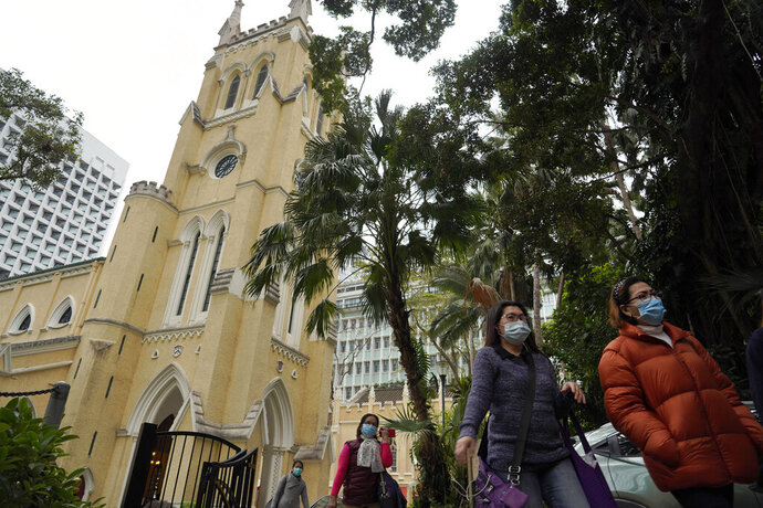 In this Feb. 9, 2020, photo, church goers wearing face masks walk out of the St John's Cathedral after attending a mass in Hong Kong. People who troop to churches and chapels were asked to wear protective masks and keep some distance to each other in Hong Kong. (AP Photo/Vincent Yu)