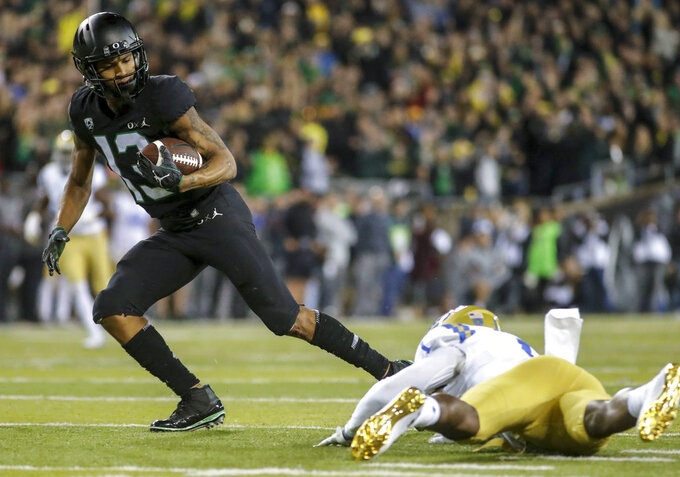 Oregon wide receiver Dillon Mitchell (13), escapes a tackle in the fourth quarter and runs in for a touchdown against UCLA during an NCAA college football game in Eugene, Ore., Saturday, Nov. 3, 2018 (AP Photo/Thomas Boyd)