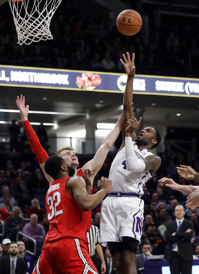 Northwestern forward Vic Law, right, shoots over Ohio State guard Keyshawn Woods, left, and forward Kyle Young during the second half of an NCAA college basketball game Wednesday, March 6, 2019, in Evanston, Ill. (AP Photo/Nam Y. Huh)