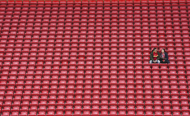 People sit surrounded by empty seats as they wait for the start of the English Premier League soccer match between Liverpool and Bournemouth at Anfield stadium in Liverpool, England, Saturday, March 7, 2020. (AP Photo/Jon Super)