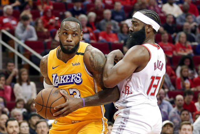 Los Angeles Lakers forward LeBron James (23) bumps Houston Rockets guard James Harden (13) as he drives to the basket during the first half of an NBA basketball game Saturday, Jan. 18, 2020, in Houston. (AP Photo/Michael Wyke)