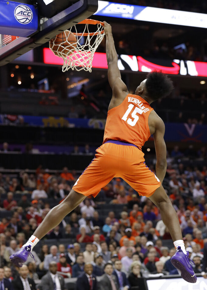 Clemson's John Newman III (15) hangs on the rim after a dunk against North Carolina State during the first half of an NCAA college basketball game in the Atlantic Coast Conference tournament in Charlotte, N.C., Wednesday, March 13, 2019. (AP Photo/Chuck Burton)
