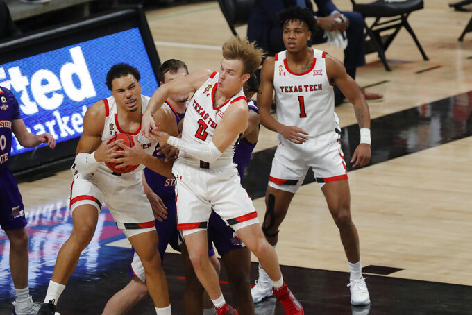 Texas Tech forward Marcus Santos-Silva, left, and guard Mac McClung bring down a rebound during the first half of the team's NCAA college basketball game against Northwestern State, Wednesday Nov. 25, 2020, in Lubbock, Texas. (AP Photo/Mark Rogers)