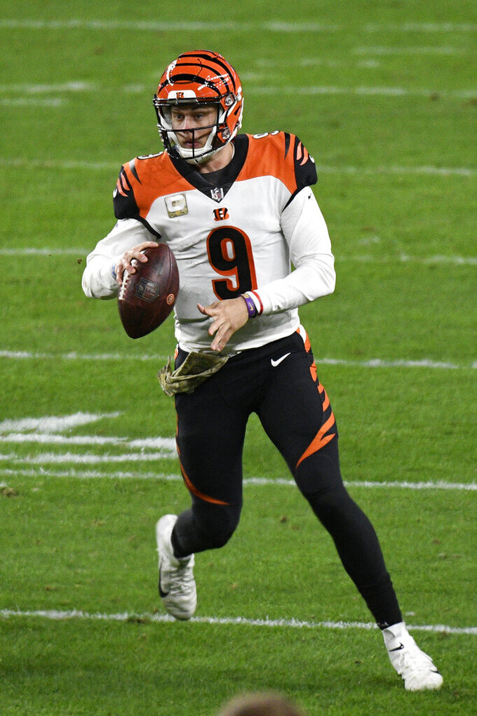Cincinnati Bengals quarterback Joe Burrow (9) rolls out of the pocket looking to pass during the first half of an NFL football game against the Pittsburgh Steelers in Pittsburgh, Sunday, Nov. 15, 2020. (AP Photo/Don Wright)