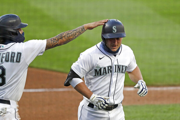 Seattle Mariners' Kyle Seager, right, is congratulated by J.P. Crawford on his three-run home run against the Los Angeles Angels in the third inning of a baseball game Wednesday, Aug. 5, 2020, in Seattle. (AP Photo/Elaine Thompson)