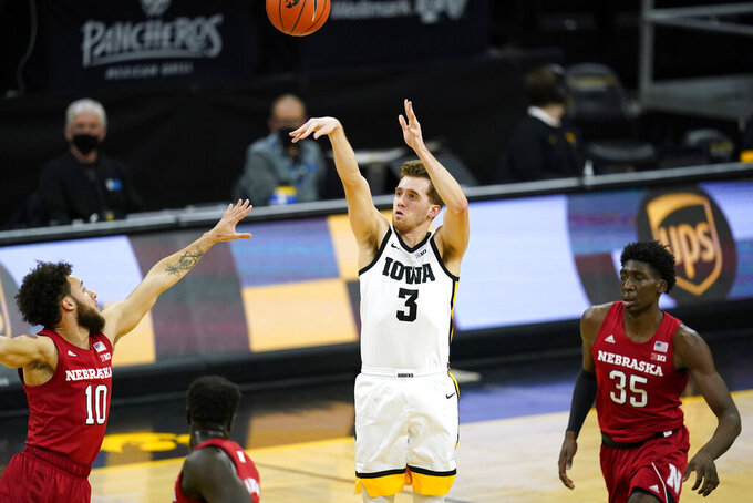 Iowa guard Jordan Bohannon (3) shoots a 3-point basket between Nebraska guard Kobe Webster, left, and center Eduardo Andre, right, during the first half of an NCAA college basketball game, Thursday, March 4, 2021, in Iowa City, Iowa. (AP Photo/Charlie Neibergall)