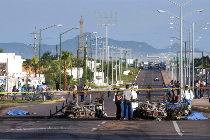 FILE - In this Sept. 30, 2016 file photo, police investigators examine the site where a military convoy was ambushed with grenades and high-powered guns, killing five soldiers in the city of Culiacan, Mexico. Local military commander Gen. Alfonso Duarte said it is very probable that the attack was carried out by the sons of imprisoned drug lord Joaquin