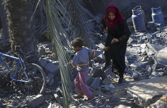Palestinians walk amid the rubble of their family house following overnight Israeli missile strikes, in Al-Qarara, east of Khan Younis, southern Gaza Strip, Thursday, Nov. 14, 2019. (AP Photo/Adel Hana)