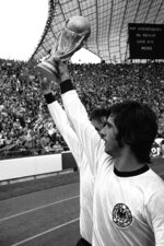 FILE - In this July 7, 1974 file photo West German forward Gerd Mueller, holds the World Cup aloft with a teammate while walking around the Olympic stadium after West Germany beat Holland 2-1 in the Football World Cup Final game in Munich, Germany. Bayern Munich and former West Germany forward Gerd Müller has died at age 75.  Mueller joined the Bavarian club in 1964 and won four league titles and four German Cup titles. Mueller helped West Germany win the European Championship in 1972, then the World Cup two years later. (AP Photo, file)
