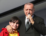 Turkey's President Recep Tayyip Erdogan reacts with a young boy as he addresses the supporters of his ruling Justice and Development Party during a rally in Kocaeli, Turkey, Tuesday, March 19, 2019. Ignoring widespread criticism, Erdogan on Tuesday again showed excerpts of a video taken by the attacker who killed 50 people in mosques in New Zealand, to denounce rising hatred and prejudice against Islam. (Presidential Press Service via AP, Pool)