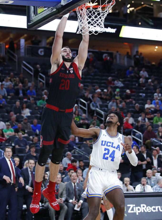 Stanford's Josh Sharma dunks over UCLA's Jalen Hill during the second half of an NCAA college basketball game in the first round of the Pac-12 men's tournament, Wednesday, March 13, 2019, in Las Vegas. (AP Photo/John Locher)