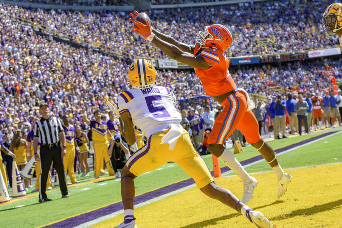Florida wide receiver Justin Shorter (4) scores a touchdown against LSU safety Jay Ward (5) in the first half of an NCAA college football game in Baton Rouge, La., Saturday, Oct. 16, 2021. (AP Photo/Matthew Hinton)