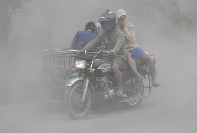 In this Jan. 13, 2020, photo,  a family rides their motorcycle through clouds of ash as they evacuate to safer grounds as Taal volcano in Tagaytay, Cavite province, southern Philippines. Red-hot lava is gushing from the volcano after a sudden eruption of ash and steam that forced residents to flee and shut down Manila's airport, offices and schools. (AP Photo/Aaron Favila, File)