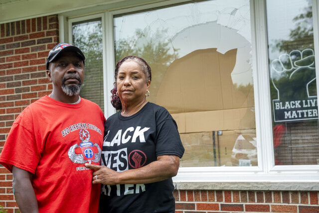 Eddie Hall Jr. and his wife Candace stand in front of the broken front window of their Warren, Mich., home, on Thursday, Sept. 10, 2020. An arrest has been made in connection with vandalism and shots fired into the couple's home. Warren Police Commissioner Bill Dwyer confirmed the arrest Tuesday night, Sept. 29 but didn't elaborate on charges or the person arrested. (David Guralnick/Detroit News via AP)
