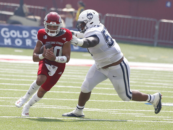 Fresno State quaterback Logan Fife, left, is chased down by Connecticut defensive lineman Travis Jones during the second half of an NCAA college football game in Fresno, Calif., Saturday, Aug. 28, 2021. (AP Photo/Gary Kazanjian)