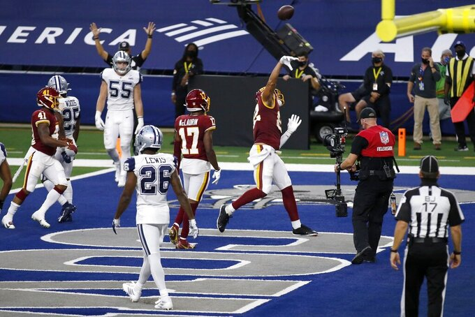 Dallas Cowboys' Jourdan Lewis (26), Leighton Vander Esch (55) and others look on as Washington Football Team tight end Logan Thomas (82) throws the ball into the seats after scoring a touchdown in the first half of an NFL football game in Arlington, Texas, Thursday, Nov. 26, 2020. (AP Photo/Roger Steinman)