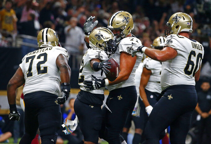 In this Oct. 8, 2018 file photo New Orleans Saints running back Mark Ingram, second left, celebrates his touchdown carry with offensive tackle Ryan Ramczyk, offensive tackle Terron Armstead (72) and center Max Unger (60) in the first half of an NFL football game against the Washington Redskins in New Orleans. The Saints have all five starters on their recently banged-up offensive line practicing as they prepare for their playoff opener against the defending champion Philadelphia Eagles on Sunday, Jan. 13, 2019. Terron Armstead says he was encouraged by his practice in more than two weeks. But he isn't yet certain he'll play as he tries to come back from a chest injury. (AP Photo/Butch Dill, file)
