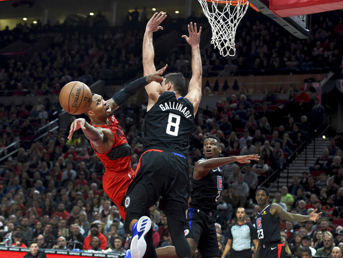 Portland Trail Blazers guard Damian Lillard, left, passes the ball as he runs into Los Angeles Clippers forward Danilo Gallinari during the second half of an NBA basketball game in Portland, Ore., Thursday, Nov. 8, 2018. The Blazers won 116-105. (AP Photo/Steve Dykes)