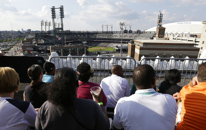 FILE - In this July 12, 2013, file photo, baseball fans watch from the roof of the Detroit Opera House before a baseball game between the Detroit Tigers and the Texas Rangers in Detroit. This week, Major League Baseball players and owners reached an agreement to play an abbreviated, 60-game season that would start July 23 or 24 in teams' home ballparks. But the seats will be empty. Instead, fans hoping to see a game in person will be have to settle for pressing their faces up against hotel windows, squinting through metal grates or climb to rooftops when baseball returns this month in otherwise empty stadiums. (AP Photo/Carlos Osorio, File)