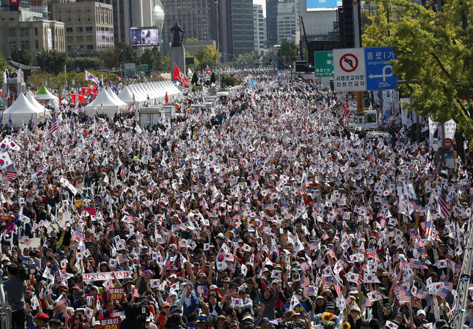 Demonstrators wave national flags of South Korea and the U.S. during a rally in Seoul, South Korea, Wednesday, Oct. 9, 2019. Thousands of protesters rallied Wednesday in South Korea's capital for the second consecutive week to call for the ouster of President Moon Jae-in's hand-picked justice minister, whose family is at the center of an investigation into allegations of financial crimes and academic favors. (AP Photo/Lee Jin-man)