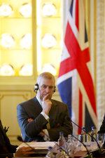 """FILE - In this file photo dated Wednesday, March 4, 2015, Britain's Prince Andrew listens as he sits at the top of the table with Mexican President Enrique Pena Nieto and various political leaders during a business breakfast meeting at Buckingham Palace in London.  Britain's Prince Andrew said Wednesday Nov. 20, 2019, that he is stepping back from public duties with the queen's permission, saying that recent disclosures regarding his association with the late convicted sex offender Jeffrey Epstein have become a """"major distraction"""" to the royal family's work. (AP Photo/Matt Dunham, FILE)"""