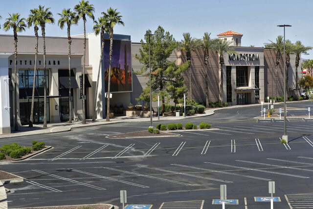 Idle businesses and empty parking lots are shown Saturday, April 4, 2020, in Chandler, Ariz. The outbreak of the coronavirus has dealt a shock to the global economy with unprecedented speed and retail stores may have been changed forever by the outbreak. (AP Photo/Matt York)