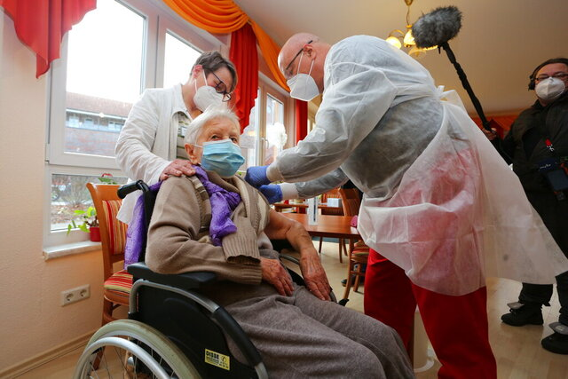 Doctor Bernhard Ellendt, right, injects the COVID-19 vaccine to nursing home resident Edith Kwoizalla, 101 years old, in Halberstadt, Germany, Saturday, Dec. 26, 2020. The first shipments of coronavirus vaccines have arrived across the European Union as authorities prepared to begin administering the first shots to the most vulnerable people in a coordinated effort on Sunday. The vaccines developed by BioNTech and Pfizer arrived by truck in warehouses across the continent on Friday and early Saturday after being sent from a manufacturing center in Belgium before Christmas. (Matthias Bein/dpa Via AP)