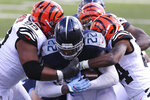 Tennessee Titans' Derrick Henry (22) is tackled by Cincinnati Bengals' Christian Covington (99) and Vonn Bell (24) during the first half of an NFL football game, Sunday, Nov. 1, 2020, in Cincinnati. (AP Photo/Jay LaPrete)
