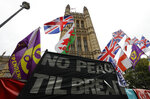 Various flags and banners fly in front of Parliament in London, Friday, Oct. 25, 2019. Politicians in Britain and the European Union seem to be looking to each other to break the Brexit deadlock. (AP Photo/Kirsty Wigglesworth)