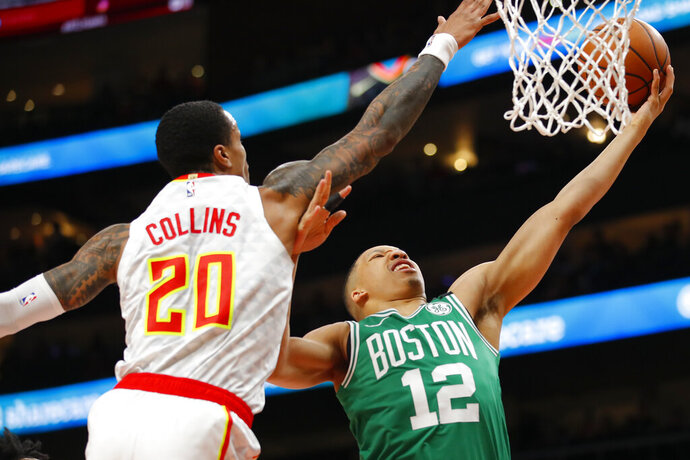 Boston Celtics forward Grant Williams (12) goes up for the shot as Atlanta Hawks forward John Collins (20) defends in the first half of an NBA basketball game on Monday, Feb. 3, 2020, in Atlanta. (AP Photo/Todd Kirkland)