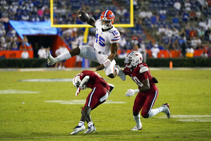 Florida quarterback Anthony Richardson (15) hurdles Florida Atlantic defensive back Justin McKithen (11) and safety Armani-Eli Adams (30) during the second half of an NCAA college football game Saturday, Sept. 4, 2021, in Gainesville, Fla. (AP Photo/John Raoux)