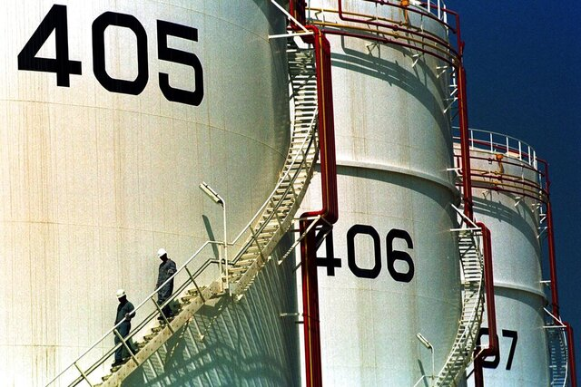 FILE- In this Sept. 25, 2000 file photo, two workers climb down from one of the tanks in an oil tank-farm in Jebel Ali, 25 miles (40 km) south of Dubai in the United Arab Emirates. The historic crash in oil prices in the wake of the novel coronavirus pandemic is reverberating across the Middle East as crude-dependent countries scramble to offset losses from a key source of state revenue. The economies of all the Arab Gulf oil exporters are expected to contract this year. (AP Photo/Kamran Jebreili, File)