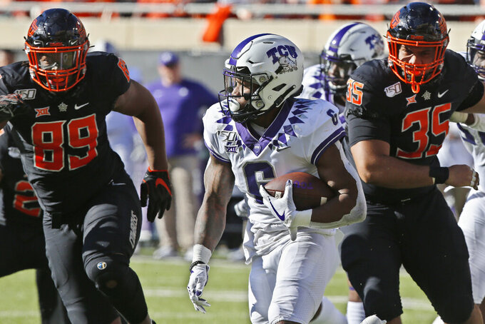 TCU running back Darius Anderson (6) carries past Oklahoma State defensive end Tyler Lacy (89) and defensive tackle Samuela Tuihalamaka (35) in the first half of an NCAA college football game in Stillwater, Okla., Saturday, Nov. 2, 2019. (AP Photo/Sue Ogrocki)