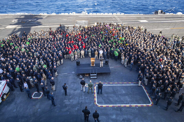 In this Dec. 15, 2019, photo U.S.Navy Capt. Brett Crozier, commanding officer of the aircraft carrier USS Theodore Roosevelt (CVN 71), addresses the crew during an all hands call on the ship's flight deck while conducting routine training in the Eastern Pacific Ocean. U.S. defense leaders are backing the Navy's decision to fire the ship captain who sought help for his coronavirus-stricken aircraft carrier, even as videos showed his sailors cheering him as he walked off the vessel. Videos went viral on social media Friday, April 3, 2020, showing hundreds of sailors gathered on the ship chanting and applauding Navy Capt. Brett Crozier as he walked down the ramp, turned, saluted, waved and got into a waiting car. (U.S. Navy Photo by Mass Communication Specialist Seaman Kaylianna Genier via AP)