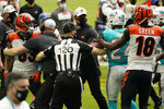 NFL side judge Jonah Monroe (120) and Cincinnati Bengals coaches attempts to stop a fight on the field during the first half of an NFL football game against the Miami Dolphins, Sunday, Dec. 6, 2020, in Miami Gardens, Fla. Cincinnati Bengals wide receiver Tyler Boyd (83) was disqualified for unnecessary roughness. (AP Photo/Lynne Sladky)
