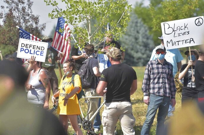 """People participate in a defend the police rally outside the Fort Collins Police Services building on Saturday, Aug. 8, 2020, in Fort Collins, Colo. Three people were arrested and another cited after fights broke out at a Colorado pro-police rally that attracted counter protesters, authorities said. The """"Back the Blue"""" rally drew hundreds of people outside the Fort Collins police department Saturday afternoon. (Kevin Lytle/Fort Collins Coloradoan via AP)"""