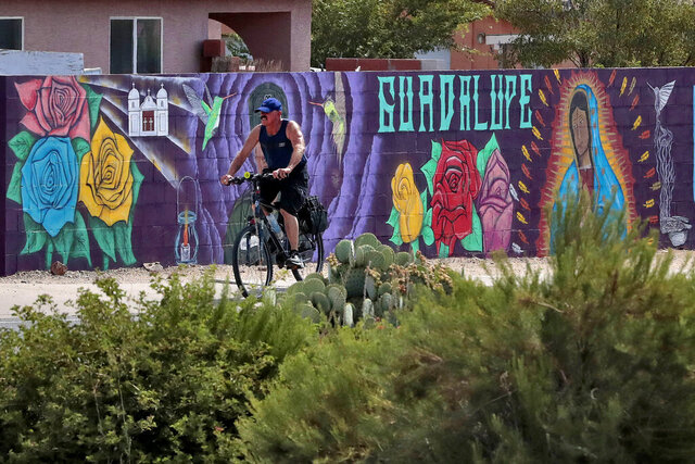 In this Saturday, June 13, 2020, photo, a man cycles past a mural in Guadalupe, Ariz. As the coronavirus spreads deeper across America, it's ravaging through the homes and communities of Latinos from the suburbs of the nation's capital to the farm fields of Florida to the sprawling suburbs of Phoenix and countless communities in between. (AP Photo/Matt York)