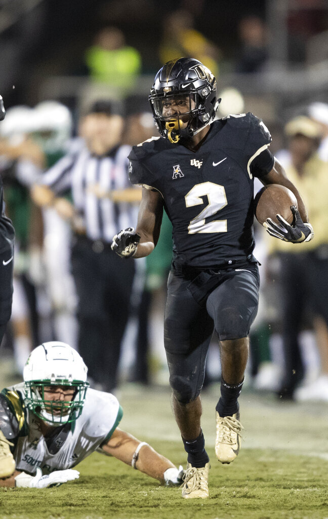 Central Florida running back Otis Anderson (2) sprints away from South Florida players during the second half of an NCAA college football game Friday, Nov. 29, 2019, in Orlando, Fla. (AP Photo/Willie J. Allen Jr.)