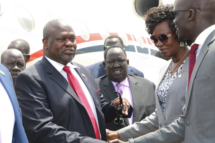 South Sudan opposition leader Riek Machar, left, is greeted by South Sudan officials as he returned to the country, Saturday, Oct.19, 2019, to meet with President Salva Kiir less than a month before their deadline to form a unity government after a five-year civil war.  Macher's two-day visit includes a scheduled meeting with the U.S. ambassador to the United Nations, who arrives Sunday with a U.N. Security Council delegation.(AP Photo/Sam Mednick)