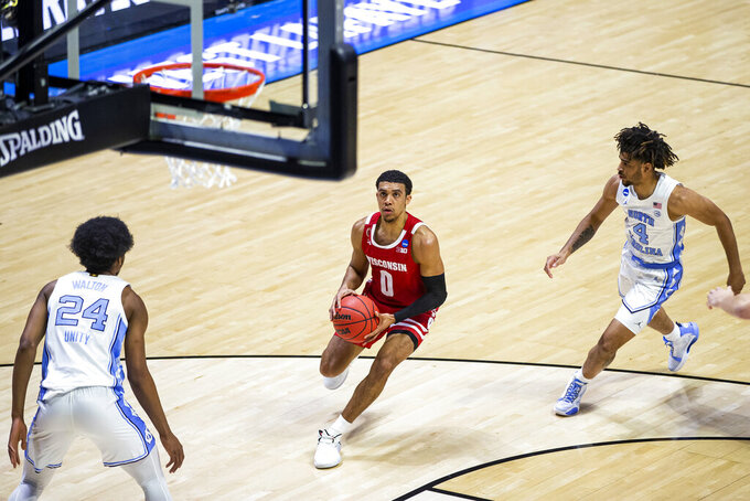 Wisconsin's Wisconsin's D'Mitrik Trice (0) drives between North Carolina's Kerwin Walton (24) and RJ Davis (4) during the first half of a first-round game in the NCAA men's college basketball tournament Friday, March 19, 2021, at Mackey Arena in West Lafayette, Ind. (AP Photo/Robert Franklin)