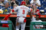 Cincinnati Reds' Jose Peraza (9) is greeted by manager David Bell, left, and Aristides Aquino (44) after scoring on a ground ball by Jose Iglesias against the Pittsburgh Pirates in the first inning of a baseball game, Friday, Sept. 27, 2019, in Pittsburgh. (AP Photo/Keith Srakocic)
