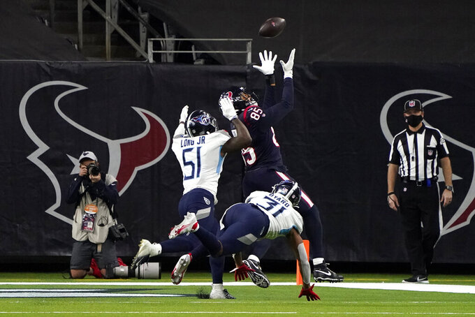 Houston Texans tight end Pharaoh Brown (85) catches a touchdown pass as Tennessee Titans' David Long Jr. (51) and Kevin Byard (31) defend during the second half of an NFL football game Sunday, Jan. 3, 2021, in Houston. (AP Photo/Eric Christian Smith)